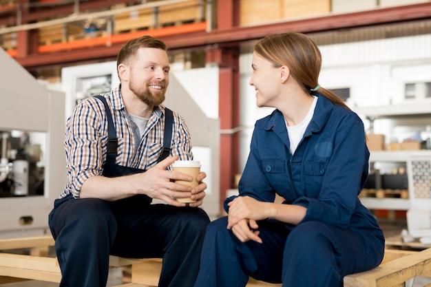 Jovens trabalhadores felizes da planta industrial sentados na oficina durante o intervalo, conversando e bebendo