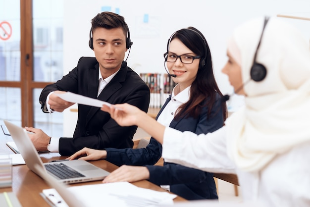 Jovens trabalham com colegas em um call center