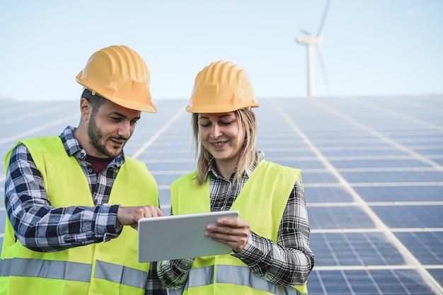 Jovens trabalhando com tablet digital em fazenda de energia renovável - foco nos rostos