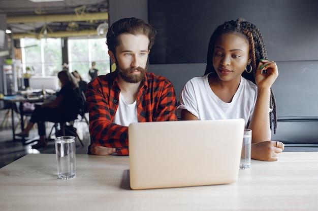 Jovens trabalhando juntos e usam o laptop