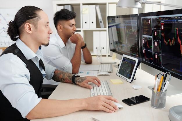 Jovens traders sérios e pensativos trabalhando na mesa do escritório, analisando as tendências do mercado de ações, comprando e vendendo ações e futuros