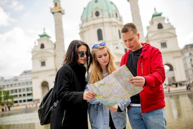 Jovens turistas com mapa de viena, áustria, perto da igreja de são pedro