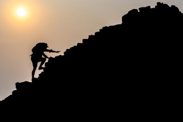 Jovens turistas do sexo masculino escalando montanhas ideias para o desenvolvimento pessoal e objetivos na vida de um alpinista com uma mochila.