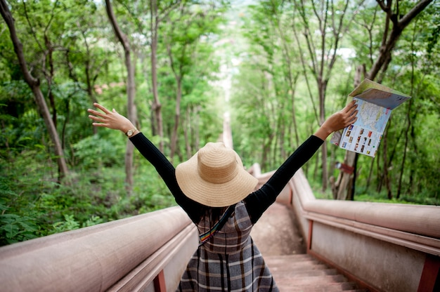 Jovens turistas e um mapa com um sorriso estão felizes em viajar para vários locais.
