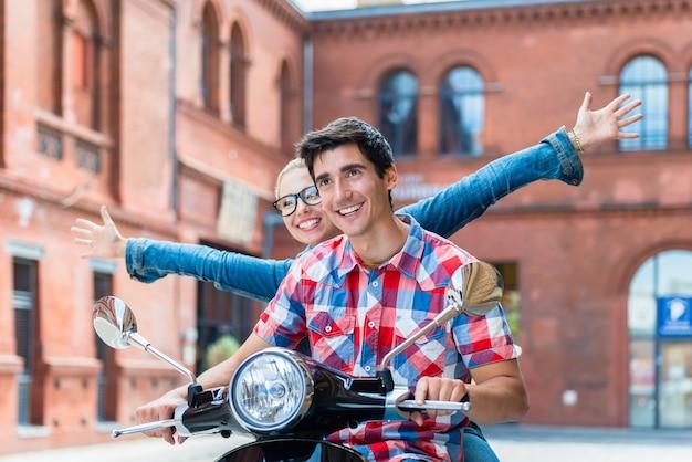 Jovens turistas fazendo excursão turística em berlim na vespa