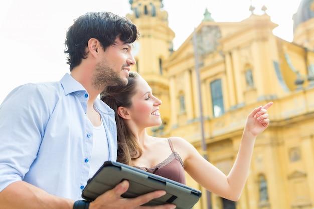 Jovens turistas na cidade com computador tablet