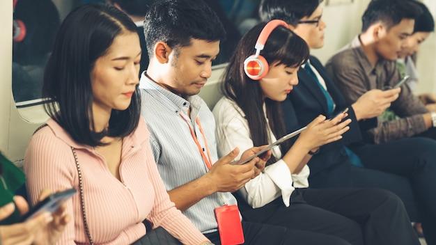 Jovens usando telefone celular em trem público subterrâneo