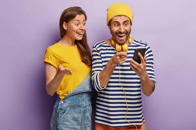 Jovens usuários femininos e masculinos otimistas de tecnologia inteligente, sentem-se bem com a atualização bem-sucedida do celular, olham para a tela, verifique o artigo