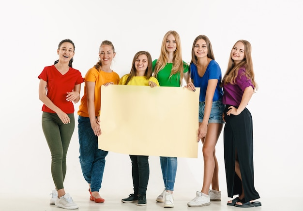 Jovens vestidos com as cores da bandeira lgbt isoladas na parede branca conceito orgulho lgbt
