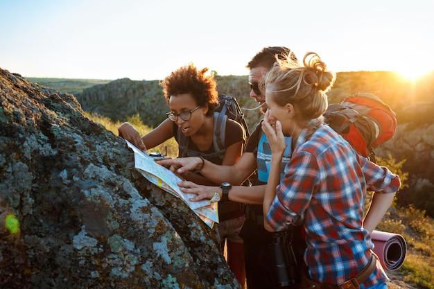 Jovens viajantes com mochilas, sorrindo, procurando a rota no mapa