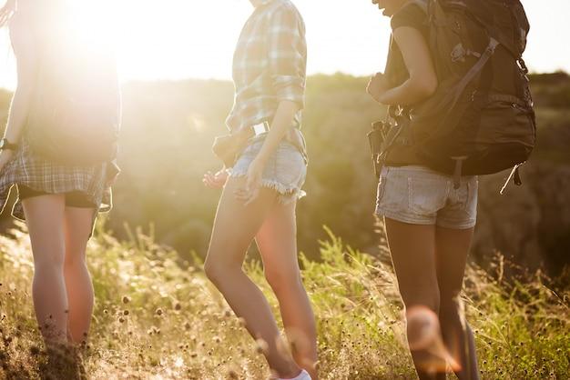 Jovens viajantes da mulher bonita andando no canyon ao pôr do sol