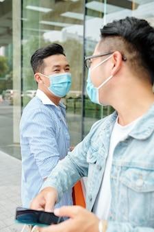 Jovens vietnamitas com máscaras médicas se cumprimentando com cotoveladas devido à pandemia de coronavírus