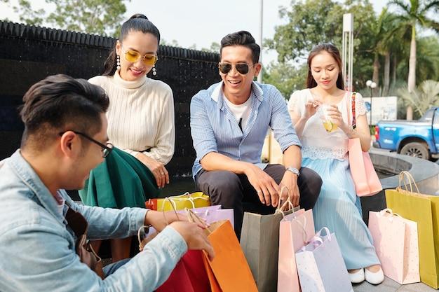 Jovens vietnamitas positivos sentados ao ar livre depois de fazer compras em um shopping e discutindo sobre compras