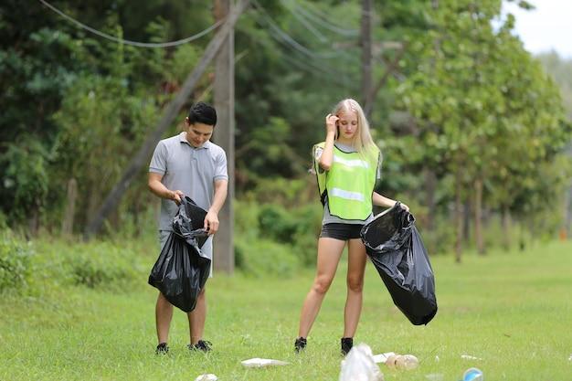 Jovens voluntários coletando garrafas plásticas para sacos de lixo no fundo da floresta.