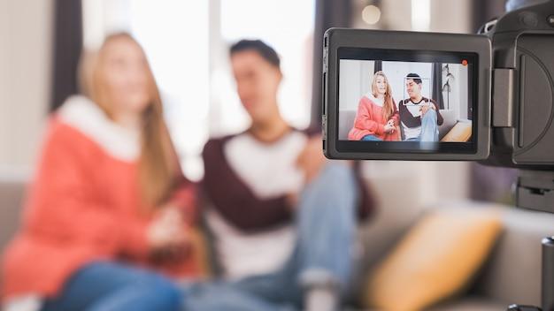 Jovens youtubers ou blogueiros criando conteúdo para mídias sociais enquanto fazem um vídeo em casa
