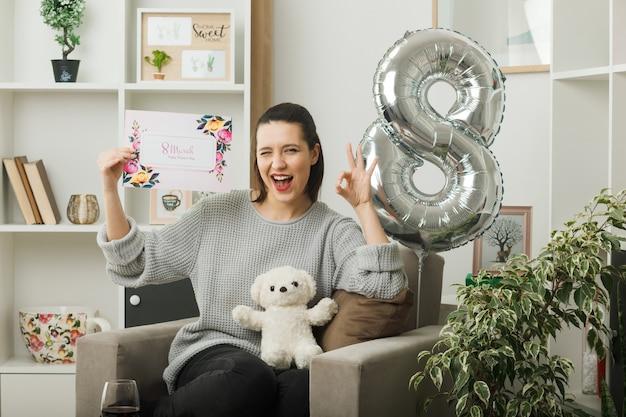 Joyful piscou mostrando gesto de ok, linda garota no dia da mulher feliz, segurando um cartão sentado na poltrona na sala de estar
