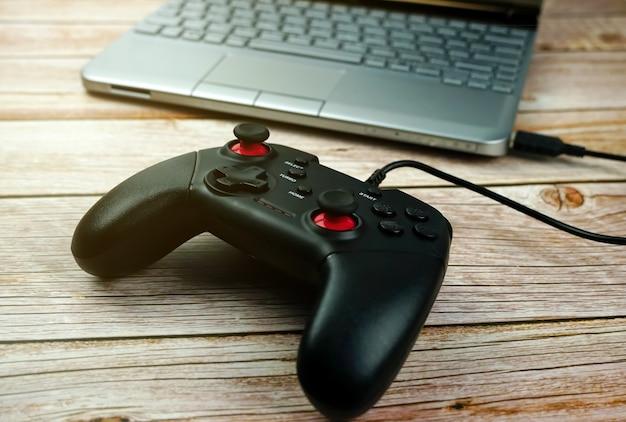 Joystick de jogo com laptop na madeira
