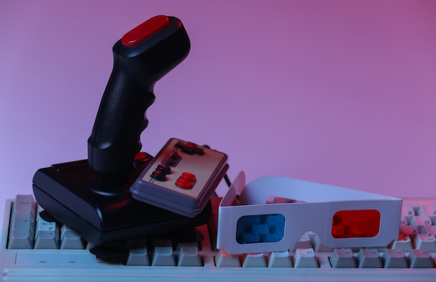 Joystick retro, gamepad com teclado de pc antigo e óculos 3d em néon gradiente rosa azul, luz holográfica. atributos anos 80, jogos, onda retro