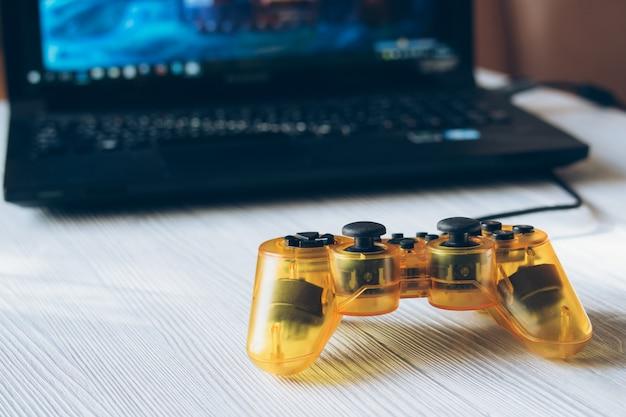 Joystick transparente amarelo e um laptop com um videogame na mesa