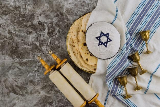 Judaica celebrando feriado de símbolos com livro sagrado religioso no rolo da torá, pão matzah israelense pesach e quatro taças para vinho