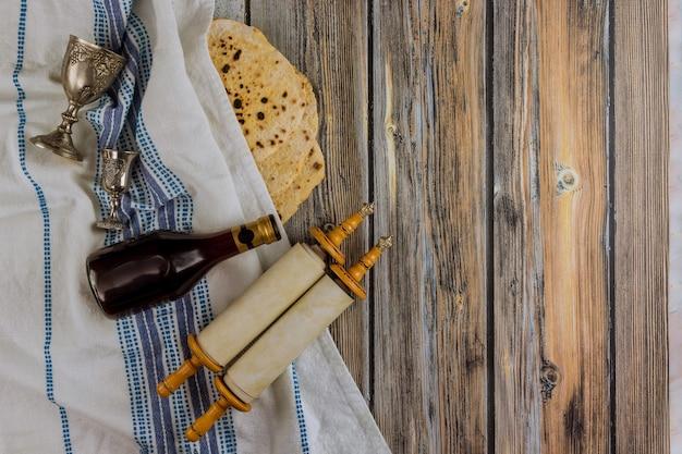 Judeu celebrando páscoa em família matzoh pães ázimos judaicos com prato tradicional de seder, quatro xícaras de vinho kosher e torá skroll