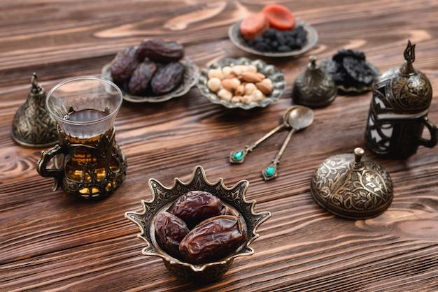 Juicy datas em tigela de ferro árabe com copo de chá na mesa de madeira