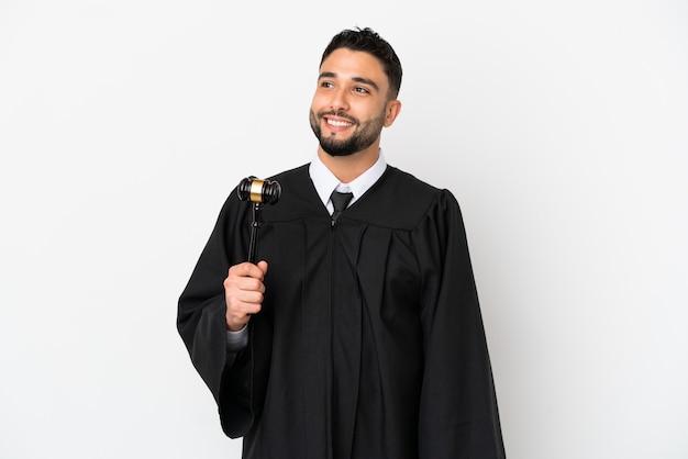 Juiz árabe isolado no fundo branco pensando em uma ideia enquanto olha para cima