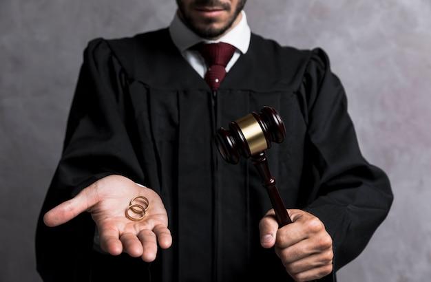 Juiz de close-up com alianças de casamento e martelo