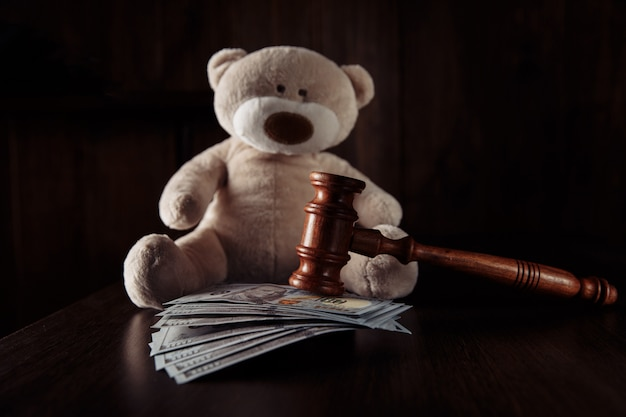 Juiz de madeira, martelo, notas de dinheiro e ursinho de pelúcia como símbolo de proteção à criança