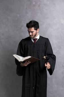 Juiz de vista frontal com livro de leitura de martelo
