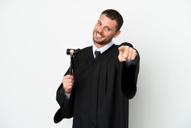 Juiz, homem caucasiano, isolado no fundo branco, apontando para a frente com uma expressão feliz