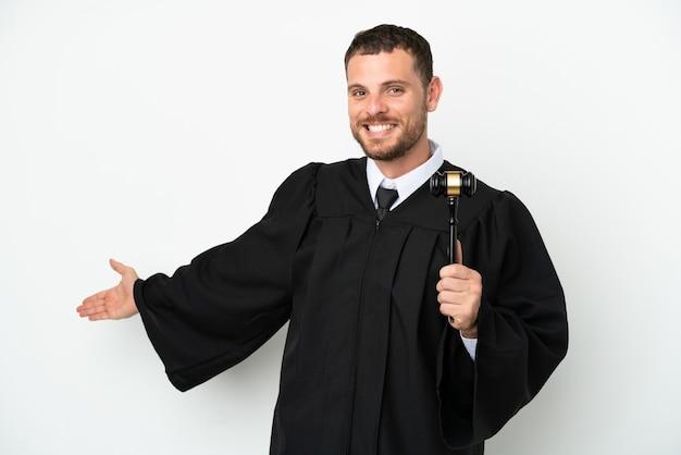 Juiz, homem caucasiano, isolado no fundo branco, estendendo as mãos para o lado para convidar para vir