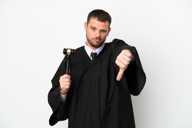 Juiz, homem caucasiano, isolado no fundo branco, mostrando o polegar para baixo com expressão negativa