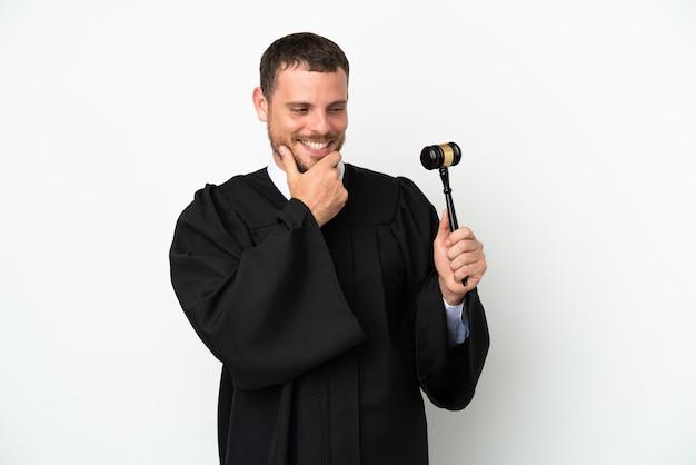 Juiz homem caucasiano isolado no fundo branco, olhando para o lado e sorrindo