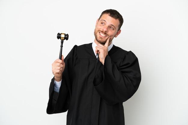 Juiz homem caucasiano isolado no fundo branco pensando uma ideia enquanto olha para cima