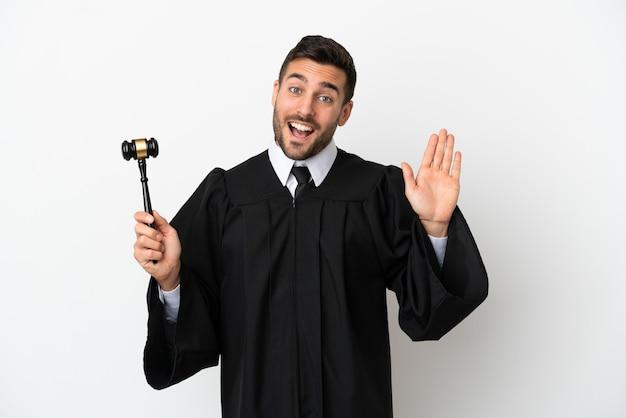 Juiz, homem caucasiano, isolado no fundo branco, saudando com a mão com expressão feliz