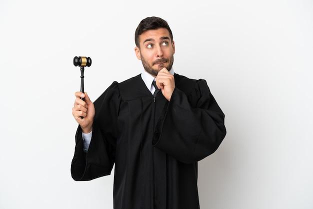 Juiz homem caucasiano isolado no fundo branco, tendo dúvidas e pensando