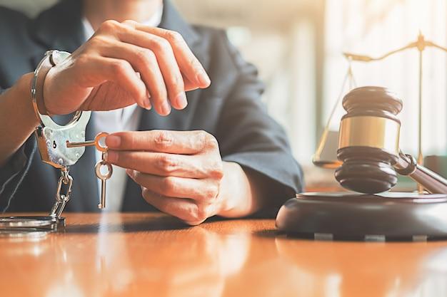 Juiz martelo e advogado de justiça algemado que segurando chave para oferecer soluções jurídicas para c