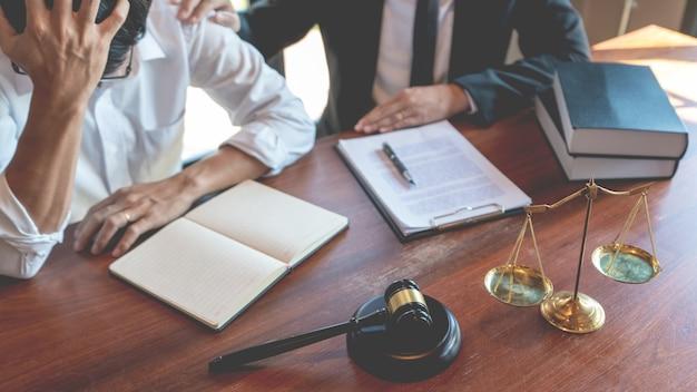 Juiz ou advogado notário masculino, consulte ou discuta papéis contratuais com um cliente empresário