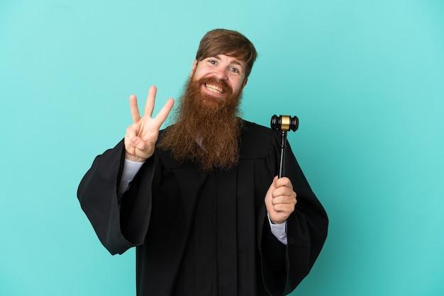 Juiz ruivo branco isolado em um fundo azul feliz e contando três com os dedos