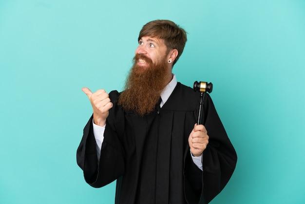 Juiz ruivo, caucasiano, isolado em um fundo azul, apontando para o lado para apresentar um produto