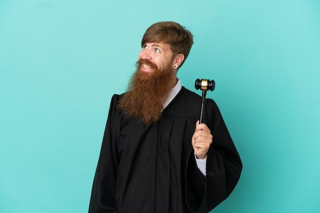 Juiz ruivo, caucasiano, isolado em um fundo azul, olhando para o lado e sorrindo