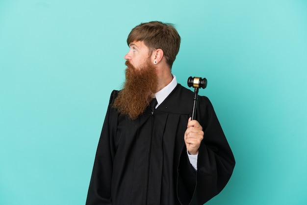 Juiz ruivo, caucasiano, isolado em um fundo azul, olhando para o lado