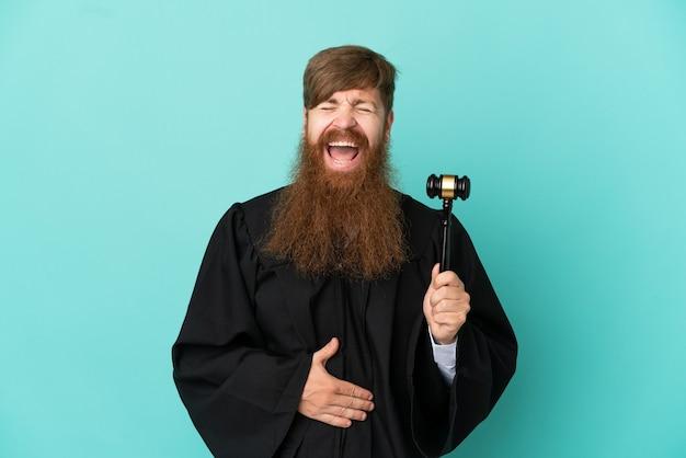 Juiz ruivo, caucasiano, isolado em um fundo azul, sorrindo muito