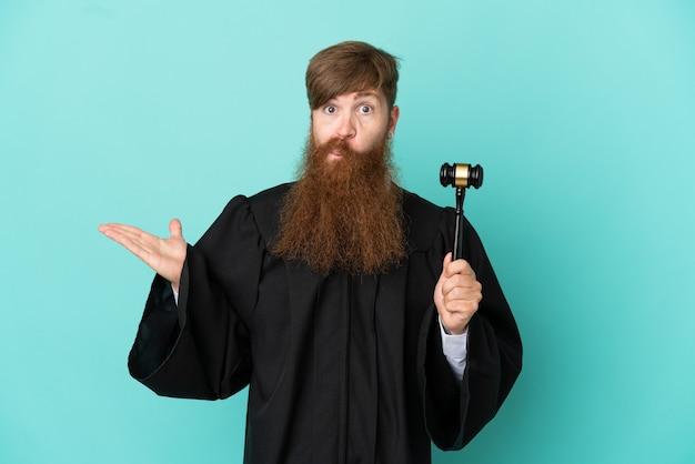 Juiz ruivo, caucasiano, isolado em um fundo azul, tendo dúvidas ao levantar as mãos