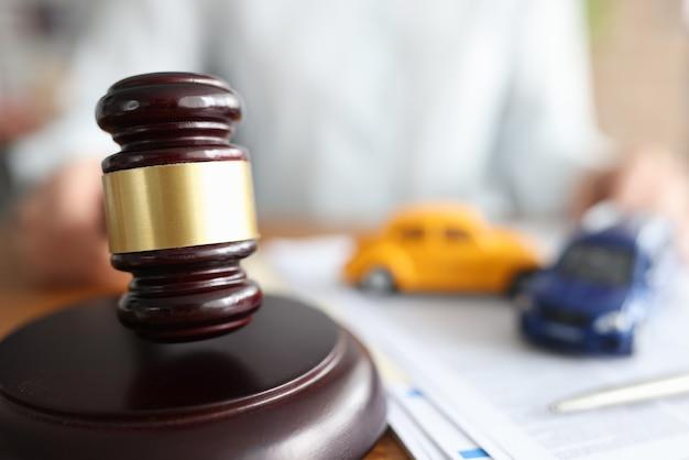 Juiz segurando um martelo perto de carros de brinquedo, close-up