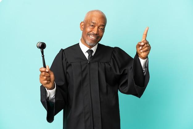 Juiz sênior isolado em fundo azul apontando uma ótima ideia