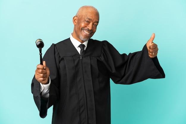 Juiz sênior isolado em fundo azul com o polegar levantado porque algo bom aconteceu