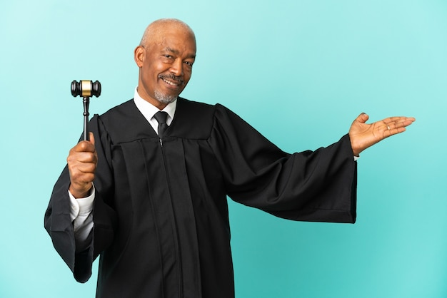 Juiz sênior isolado em fundo azul, estendendo as mãos para o lado para convidar para vir