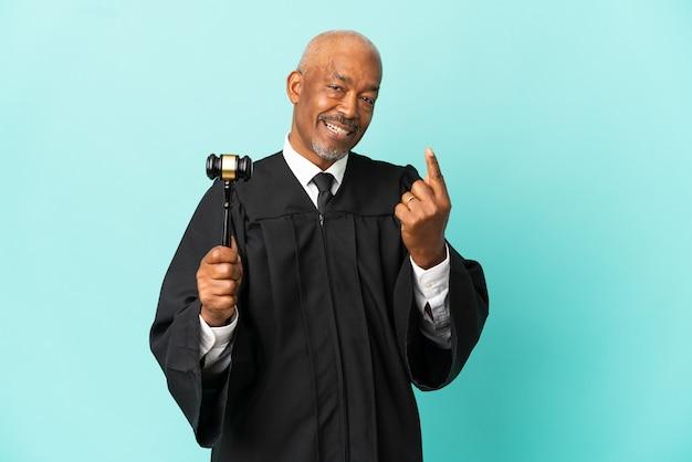 Juiz sênior isolado em fundo azul fazendo gesto de aproximação